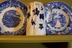 Antique flow blue pitcher and transferware plates on shelf